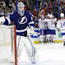 Tampa Bay Lightning goalie Anders Lindback (39), of Sweden, reaches for his water bottle as the Montreal Canadiens celebrate a goal by Brendan Gallagher during the third period of Game 2 of a first-round NHL hockey playoff series on Friday, April 18, 2014