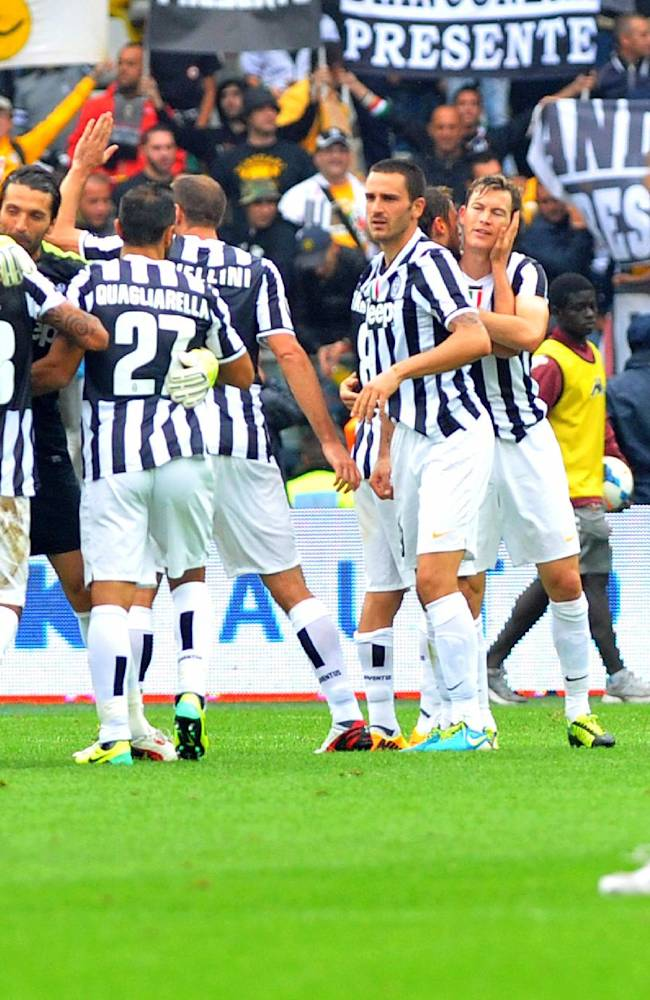 Juventus players celebrate their 1-0 win over Torino as Torino coach Giampiero Ventura, right, and Torino's Riccardo Meggiorini walk on the pitch, at the end of a Serie A soccer match at the Olympic stadium, in Turin, Italy, Sunday, Sept. 29, 2013. Juventus earned a narrow 1-0 win in a heated derby match at city rival Torino on Sunday, to move provisionally top of the table with Napoli. Paul Pogba scored a contentious 54th minute winner, heading in the rebound after Carlos Tevez's header came off the crossbar. There were fierce protests from Torino, however, as Tevez appeared to be offside