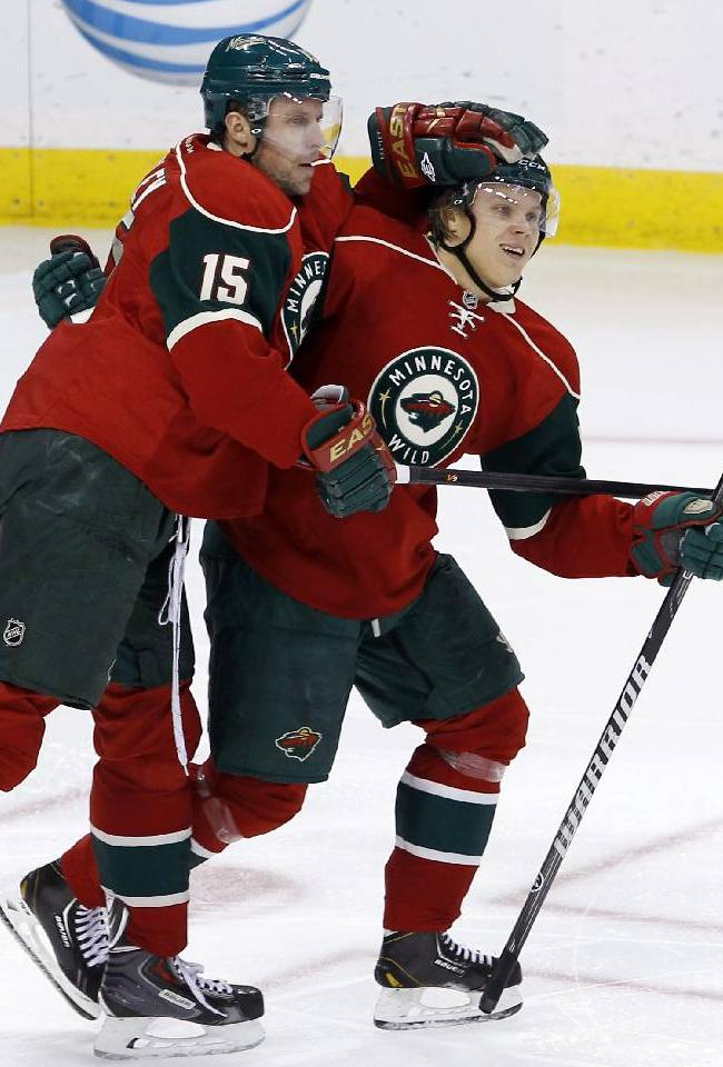 Minnesota Wild right wing Dany Heatley (15), of Germany, and Minnesota Wild center Mikael Granlund, of Finland, celebrate Heatley's goal on New Jersey Devils goalie Cory Schneider during the third period of an NHL hockey game in St. Paul, Minn., Sunday, Nov. 3, 2013. The Wild won 4-0