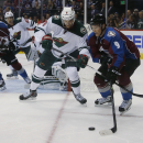 Minnesota Wild defenseman Marco Scandella, center, battles for control of puck with Colorado Avalanche center Matt Duchene, right, as defenseman Tyson Barrie, left, covers in the second period of an NHL hockey game in Denver on Saturday, Oct. 11, 2014 The