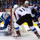 Vancouver Canucks goalie Jacob Markstrom, left, of Sweden, stops Colorado Avalanche's Jamie McGinn (11) as Nathan MacKinnon (29) and Canucks' Yannick Weber, right, of Switzerland, watch during the first period of an NHL hockey game Thursday, April 10, 201