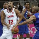 France's Tony Parker, right, knocks the ball from the hands of Tunisia's Makram Ben Romdhane  during a men's basketball game at the 2012 Summer Olympics, Saturday, Aug. 4, 2012, in London. (AP Photo/Charles Krupa)