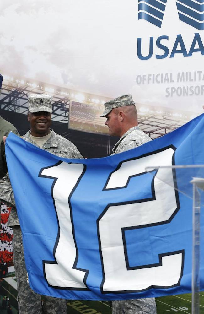 U.S. Air Force Col. Bruce Bowers, left, commander of the 446th Airlift Wing, stands with other military leaders as he holds the Seattle Seahawks