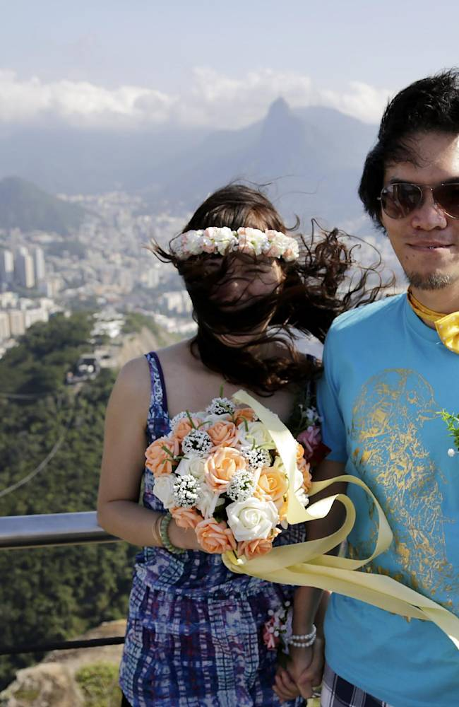 Taiwanese couple Lai Chi Jan, left, and Yu Wei Shan pose for a picture at the top of the iconic Sugarloaf mountain in Rio de Janeiro, Brazil, Monday June 9, 2014. The newlyweds are in Brazil to watch the World Cup 2014 for the whole duration of the tournament, as part of their honeymoon plans. They are supporters of the Brazil soccer team