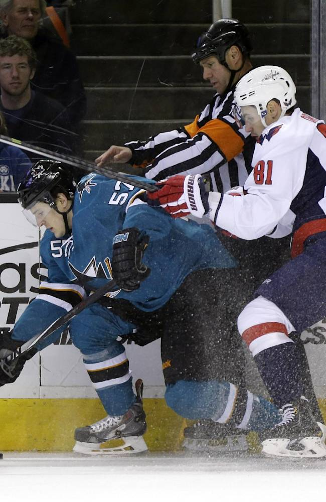 San Jose Sharks' Tommy Wingels, left, collides with a linesman and Washington Capitals' Dmitry Orlov (81), of Russia, during the first period of an NHL hockey game on Saturday, March 22, 2014, in San Jose, Calif