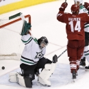 Dallas Stars' Tim Thomas, left, slams his stick down to the ice as Phoenix Coyotes' Jeff Halpern (14) celebrates a goal by teammate David Moss during the third period of an NHL hockey game on Sunday, April 13, 2014, in Glendale, Ariz. The Coyotes defeate