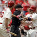 St. Louis Cardinals' Yadier Molina, right, runs into home plate umpire Mike Estabrook, center, after scoring as Cardinals' Adam Wainwright stands near during the second inning of a baseball game Saturday, April 12, 2014, in St. Louis The Associated Press