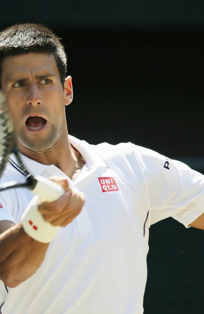 Novak Djokovic of Serbia plays a return to Grigor Dimitrov of Bulgaria during their men's singles semifinal match at the All England Lawn Tennis Championships in Wimbledon, London, Friday, July 4, 2014