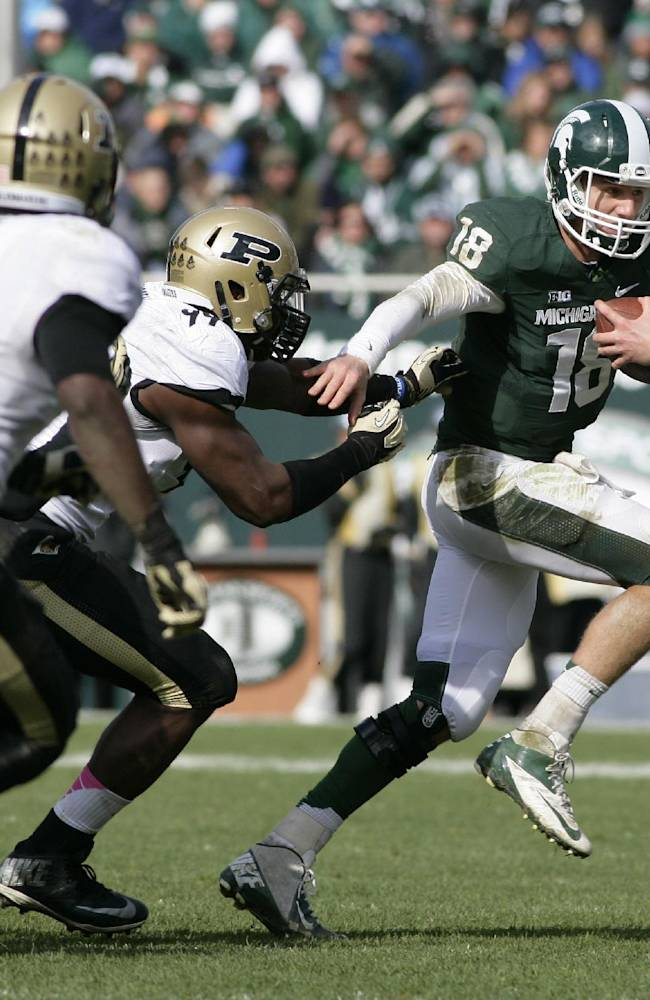 In this Oct. 19, 2013 file photo, Michigan State quarterback Connor Cook (18) scrambles against Purdue's Ryan Russell, center, and Anthony Brown (9) during the fourth quarter of an NCAA college football game in East Lansing, Mich. Heading into the final month of regular season Michigan State is battling for supremacy in the  Big Ten's Legends Division with Michigan and Nebraska