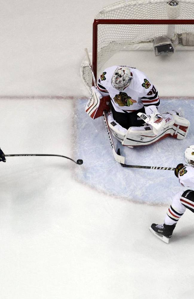 Chicago Blackhawks goalie Corey Crawford blocks a shot from St. Louis Blues' Chris Porter, left, as Blackhawks' Duncan Keith (2) and Jonathan Toews, right, watch during the first overtime in Game 1 of a first-round NHL hockey Stanley Cup playoff series Thursday, April 17, 2014, in St. Louis