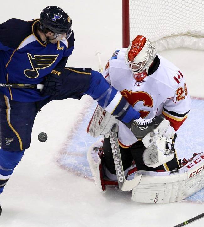St. Louis Blues' David Backes, left, tries to avoid the puck as Calgary Flames goalie Reto Berra, of Switzerland, defends during the first period of an NHL hockey game Thursday, Nov. 7, 2013, in St. Louis