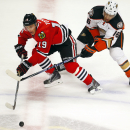 Chicago Blackhawks center Jonathan Toews (19) and Anaheim Ducks right wing Emerson Etem (16) go after the puck during the third period of an NHL hockey game Tuesday, Oct. 28, 2014, in Chicago. The Ducks won 1-0 The Associated Press