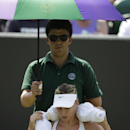 Maria Sharapova of Russia wraps a towel around her neck as she is sheltered from the sun during a break from play of the singles match against Richel Hogenkamp of the Netherlands, at the All England Lawn Tennis Championships in Wimbledon, London, Wednesday July 1, 2015. (AP Photo/Pavel Golovkin)