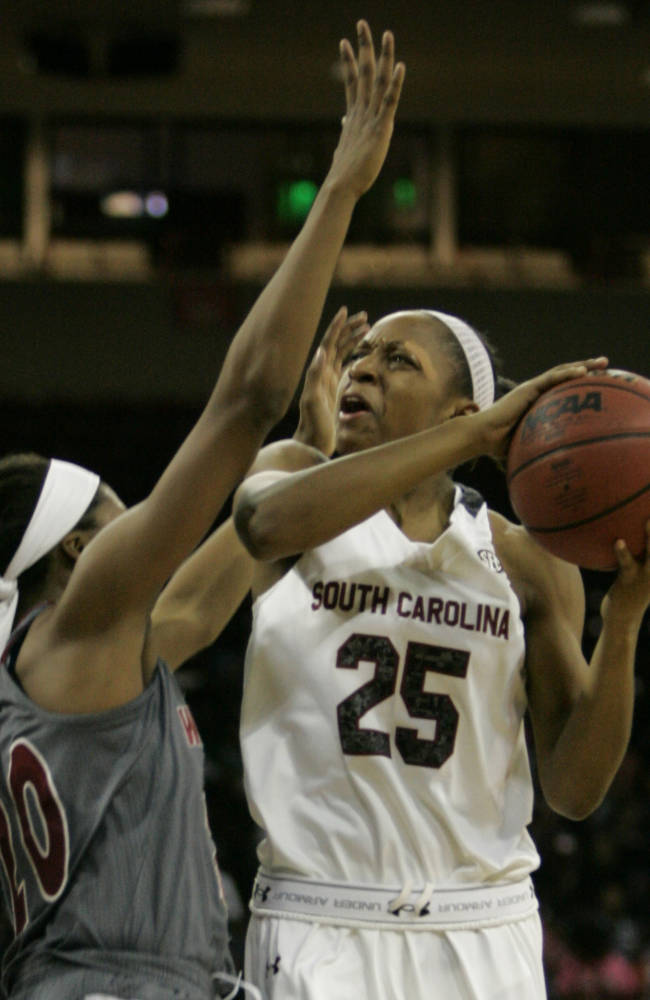 South  Carolina's Tiffany Mitchell (25 drives for the basket as Winthrop's Taylor Calvert (20) tries to block during the first half of their NCAA college basketball game Friday, Dec. 20, 2013, in Columbia, SC. Mitchell had 20 total points as South Carolina defeated Winthrop 69-61