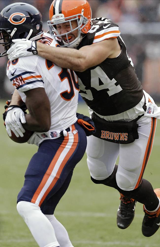 Cleveland Browns tight end Jordan Cameron (84) tackles Chicago Bears cornerback Zack Bowman after an interception in the first half of an NFL football game, Sunday, Dec. 15, 2013, in Cleveland