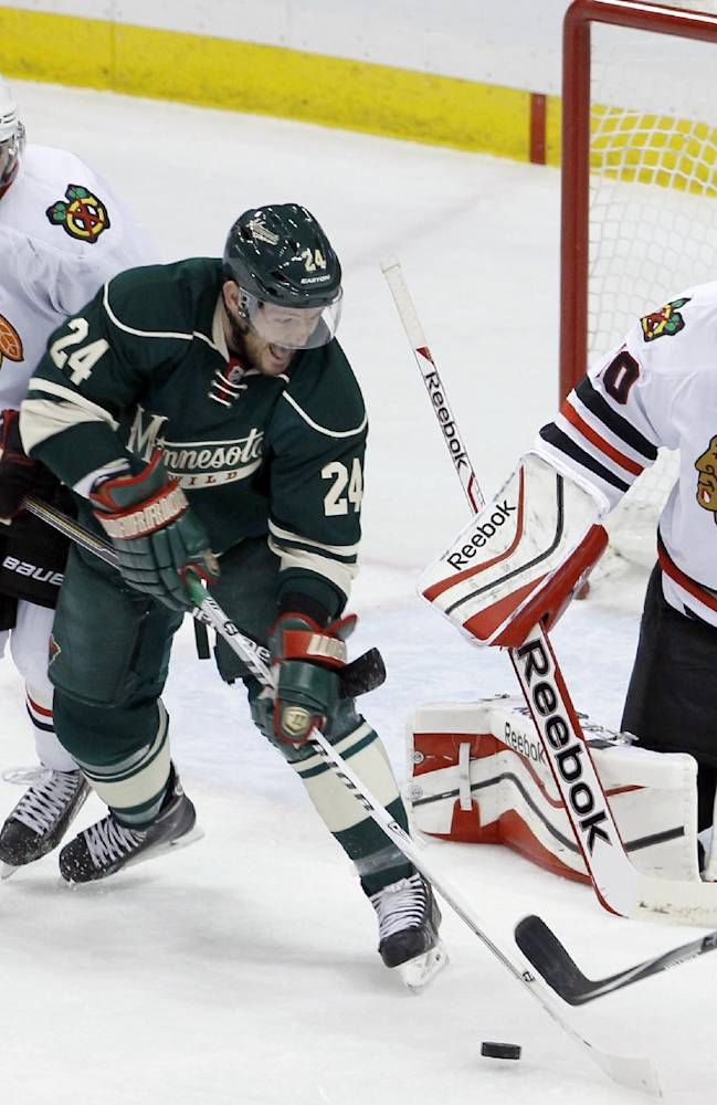 Minnesota Wild left wing Matt Cooke (24) and Chicago Blackhawks defenseman Nick Leddy (8) chase the puck as Blackhawks goalie Corey Crawford (50) covers the net during the first period of Game 6 of an NHL hockey second-round playoff series in St. Paul, Minn., Tuesday, May 13, 2014. The Blackhawks won 2-1 in overtime