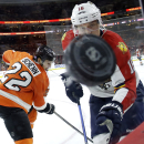 Florida Panthers' Aleksander Barkov (16), of Finland, and Philadelphia Flyers' Luke Schenn (22) chase a loose puck during the third period of an NHL hockey game, Thursday, Nov. 6, 2014, in Philadelphia. Philadelphia won 4-1 The Associated Press