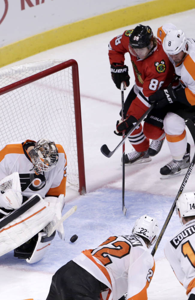 Philadelphia Flyers goalie Steve Mason, left, makes an initial save on a shot by Chicago Blackhawks defenseman Duncan Keith, but right wing Patrick Kane (88) reaches in on defenseman Nicklas Grossmann (8) and scores during the third period of an NHL hockey game Tuesday, Oct. 21, 2014, in Chicago. The Blackhawks won 4-0. Also watching the play are defenseman Luke Schenn (22) and Sean Couturier (14)