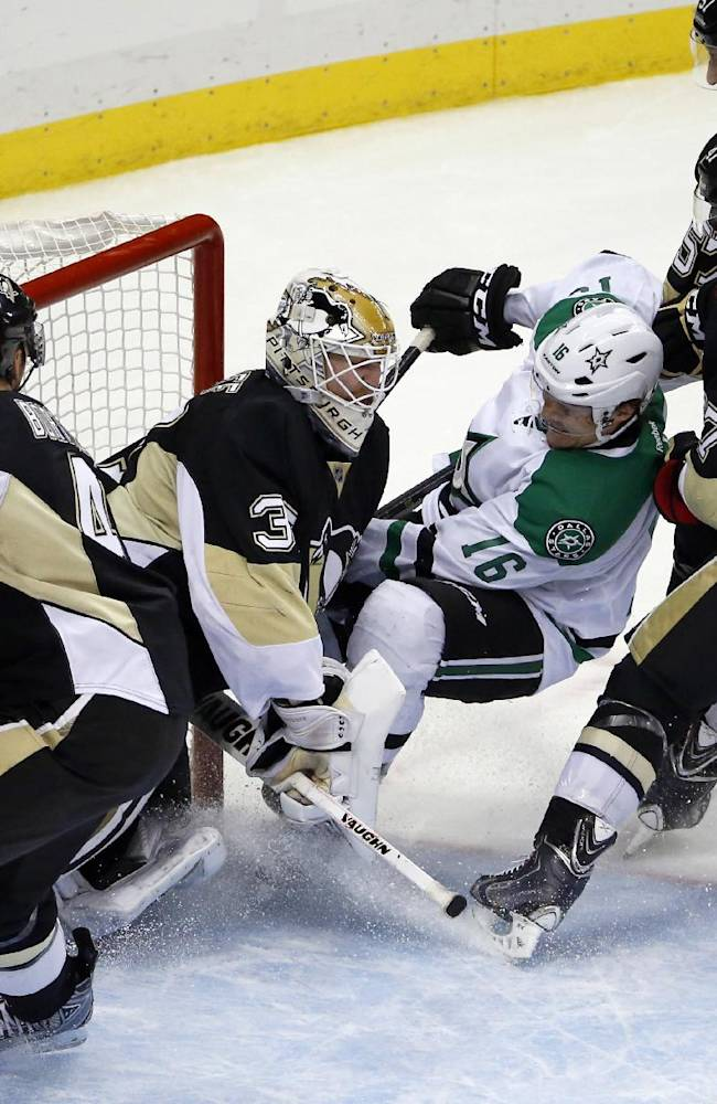 Dallas Stars' Trevor Daley (6) collides with Pittsburgh Penguins goalie Jeff Zatkoff (37) after being checked by Simon Despres (47) and Marcel Goc (57) during the third period of an NHL hockey game in Pittsburgh, Tuesday, March 18, 2014. The Penguins won 5-1