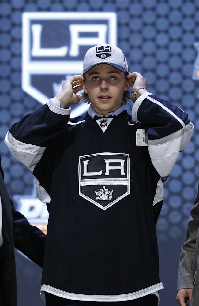 Adrian Kempe pulls on a Los Angeles Kings hat after being chosen 29th overall during the first round of the NHL hockey draft, Friday, June 27, 2014, in Philadelphia