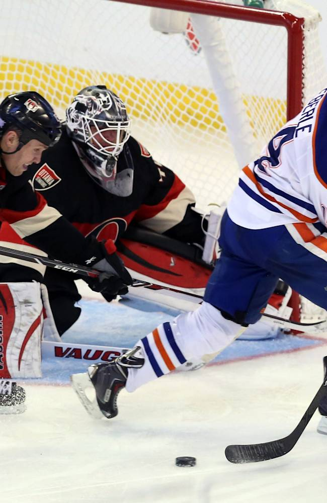 Edmonton Oilers' Jordan Eberle (14) attempts a backhand shot as he is watched by Ottawa Senators goaltender Robin Lehner (40) and Senators' Zack Smith (15)  during the third period of an NHL hockey in Ottawa, Saturday, Oct. 19, 2013