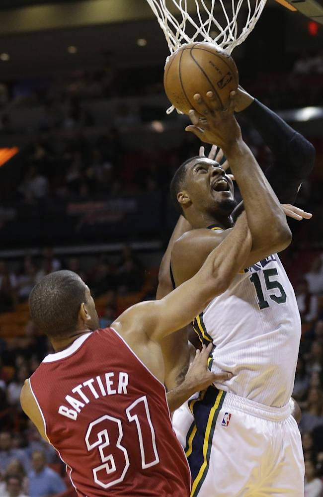 Utah Jazz's Derrick Favors (15) is fouled by Miami Heat's Shane Battier (31) in the first half of an NBA basketball game, Monday, Dec. 16, 2013, in Miami