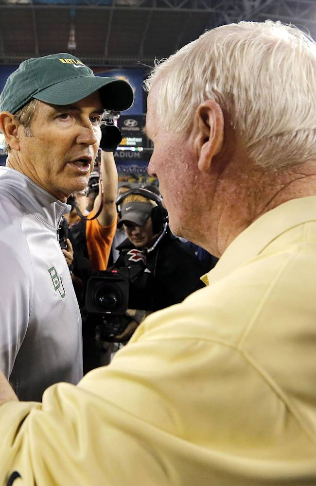 Central Florida head coach George O'Leary, right, greets Baylor head coach Art Briles at mid-field after the Fiesta Bowl NCAA college football game against Baylor, Wednesday, Jan. 1, 2014, in Glendale, Ariz. Central Florida won 52-42