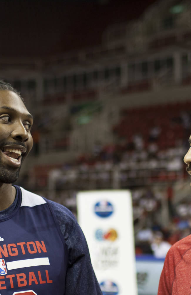 Washington Wizards forward Nene, left, and Chicago Bulls forward Carlos Boozer, chat during a NBA Fan Day event in Rio de Janeiro, Brazil, Thursday, Oct. 10, 2013. The Wizards and Bulls are in Brazil preparing for their Saturday exhibition game, NBA's first in South America
