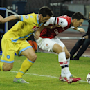 Napoli's Cristian Maggio, left, and Arsenal Ozil Mesut go for the ball during a Champions League, group F, soccer match between Napoli and Arsenal, at the Naples San Paolo stadium, Italy, Wednesday, Dec. 11, 2013