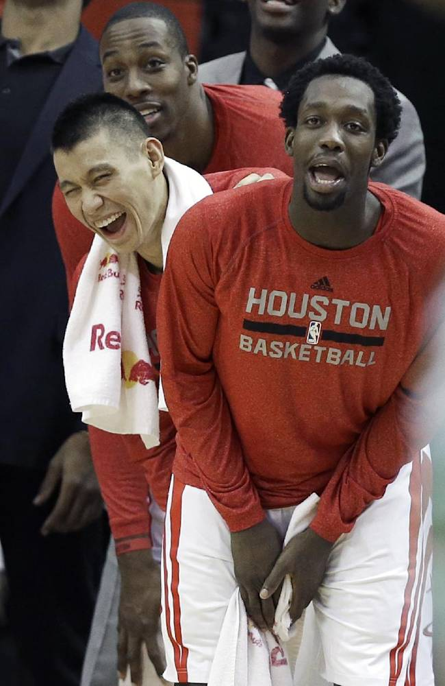 Houston Rockets Dwight Howard, left, Jeremy Lin, center, and Patrick Beverley laugh from the sidelines in the final minutes of an NBA basketball game against the Boston Celtics Tuesday, Nov. 19, 2013, in Houston. The Rockets won 109-85
