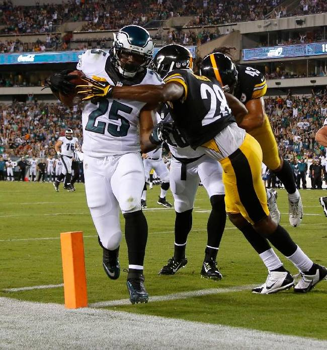 In this Aug. 21, 2014, file photo, Philadelphia Eagles' LeSean McCoy (35) scores a touchdown past Pittsburgh Steelers' Cortez Allen (28) during the first half of an NFL preseason football game in Philadelphia. Millions of people using the top three fantasy football platforms have generated three different answers to the question of the top draft pick.Yahoo says LeSean McCoy. ESPN says Adrian Peterson of Minnesota. CBS Sports says it's Jamaal Charles of Kansas City