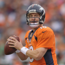 In this Sept. 29, 2013, file photo, Denver Broncos quarterback Peyton Manning (18) drops back to pass for a touchdown against the Philadelphia Eagles in the third quarter of an NFL football game in Denver. Manning's next touchdown throw will be his 500th,