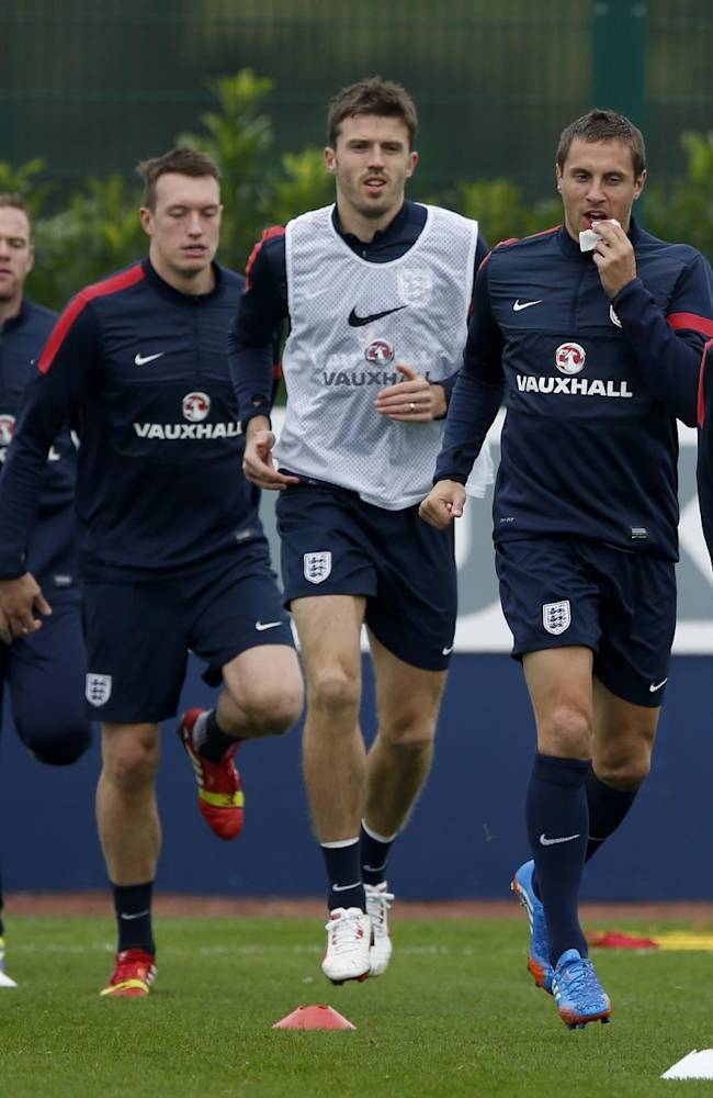 England's Phil Jagielka, third right, tries to stop his lip bleeding as he trains with, from left, Raheem Sterling, Wayne Rooney, Phil Jones, Michael Carrick, Leighton Baines and James Milner during a practice session at facilities in London Colney, England, Monday, Oct. 14, 2013. England will play Poland in a World Cup Group H qualification soccer match at Wembley stadium in London on Tuesday