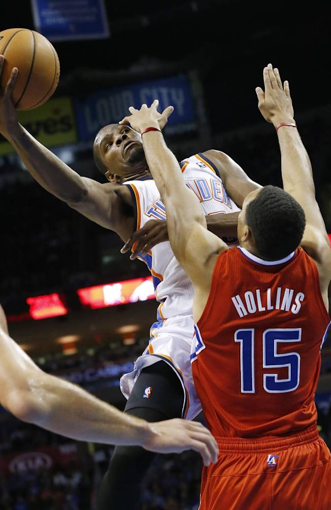 Oklahoma City Thunder forward Kevin Durant, top, shoots as Los Angeles Clippers center Ryan Hollins (15) defends in the third quarter of an NBA basketball game in Oklahoma City, Thursday, Nov. 21, 2013. Oklahoma City won 105-91