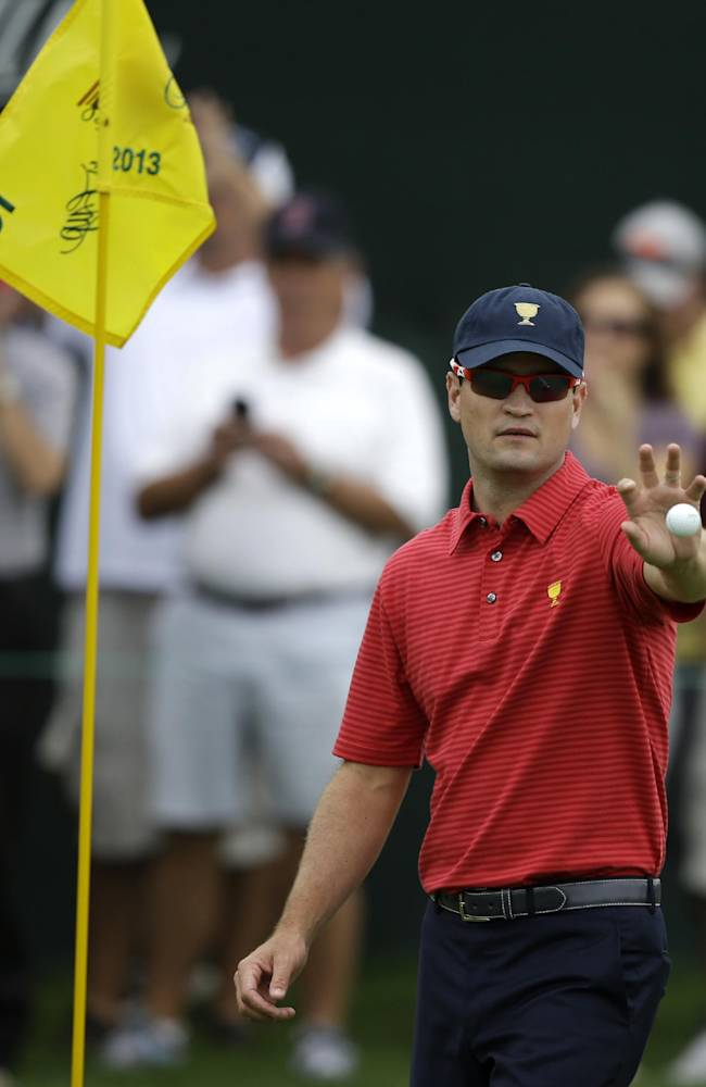 United States team player Zach Johnson catches a golf ball tossed by his caddie during a practice round for the Presidents Cup golf tournament at Muirfield Village Golf Club Wednesday, Oct. 2, 2013, in Dublin, Ohio