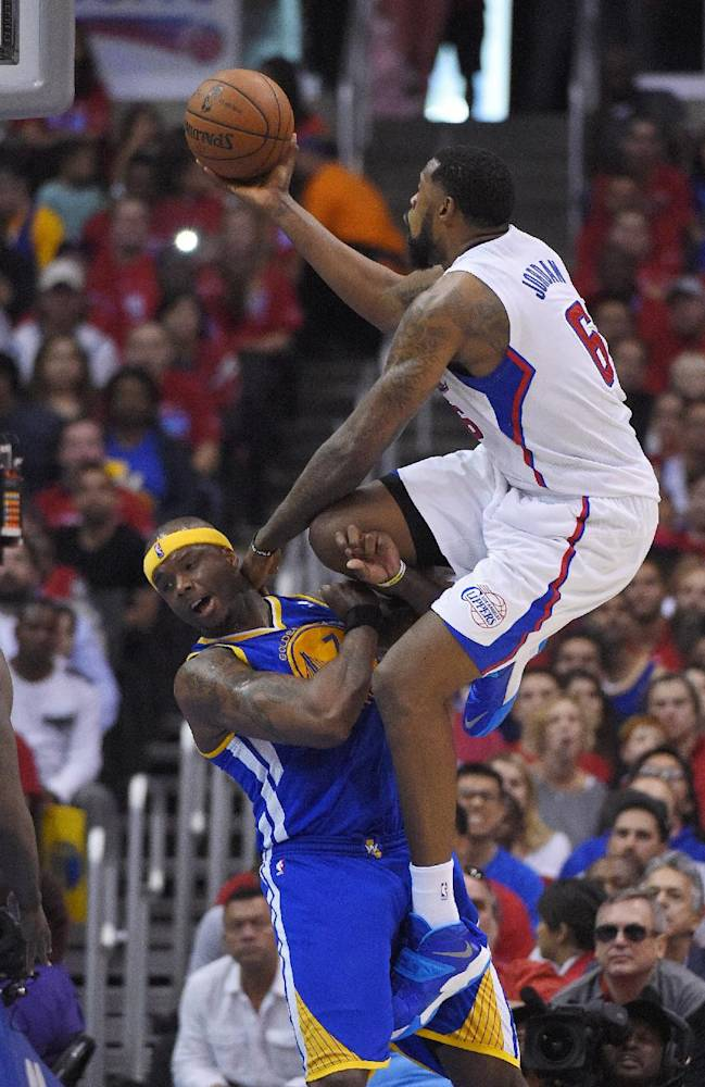 Los Angeles Clippers center DeAndre Jordan, right, puts up a shot as Golden State Warriors center Jermaine O'Neal defends during the second half in Game 1 of an opening-round NBA basketball playoff series, Saturday, April 19, 2014, in Los Angeles. The Warriors won 109-105