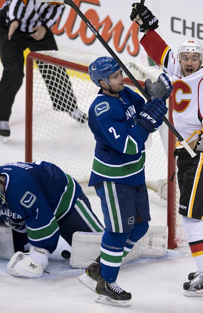Calgary Flames left wing T.J. Galiardi (39) celebrates a goal by teammate defenseman T.J. Brodie (7) on Vancouver Canucks Roberto Luongo as Canucks defenseman Dan Hamhuis (2) skates past during the third period of NHL action in Vancouver, British Columbia Saturday Jan. 18, 2014