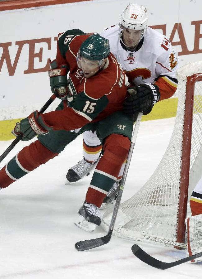 Minnesota Wild's Dany Heatley, left, cuts the corner as he is pursued by Calgary Flames' Sean Monahan as goalie Reto Berra, right, defends the net in the first period of an NHL hockey game, Monday, March 3, 2014, in St. Paul, Minn