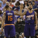 Phoenix Suns forward Marcus Morris, left, congratulates his twin brother, Markieff, after he scored against the Sacramento Kings during the fourth quarter of an NBA basketball game in Sacramento, Calif., Wednesday, April 16, 2014. The Suns won 104-99.(AP Photo/Rich Pedroncelli)