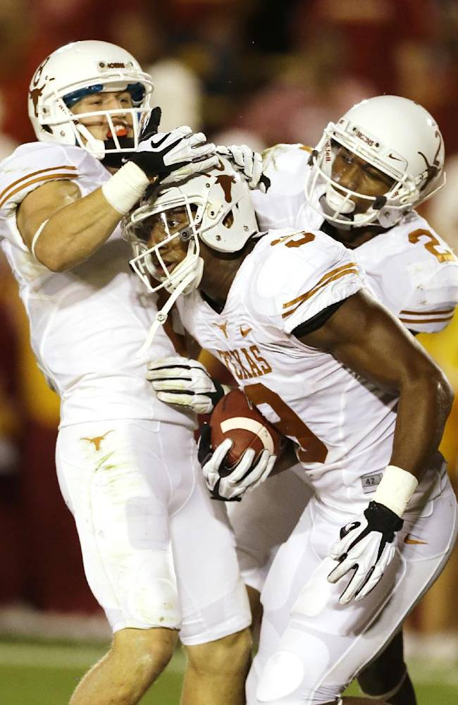 Texas tight end John Harris (9) celebrates with teammates Jaxon Shipley, left, and Kendall Sanders, right, after catching a 44-yard touchdown pass during the first half of an NCAA college football game against Iowa State, Thursday, Oct. 3, 2013, in Ames, Iowa