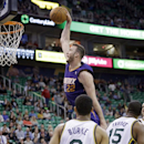 Phoenix Suns' Miles Plumlee (22) dunks the ball as Utah Jazz's Trey Burke (3) and teammate Derrick Favors (15) look on in the first quarter of an NBA basketball game on Wednesday, Feb. 26, 2014, in Salt Lake City The Associated Press