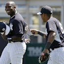 New York Yankees second baseman Yangervis Solarte, right, laughs with Yankees left fielder Alfonso Soriano, left, as they take the field between innings during a spring training baseball game against the Tampa Bay Rays in Tampa, Fla., Sunday, March 9, 201
