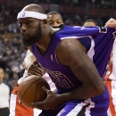 Sacramento Kings' Reggie Evans is pulled back by Toronto Raptors' Jonas Valanciunas as he drives to the net during first half NBA basketball action in Toronto on Friday, March 7, 2014 The Associated Press