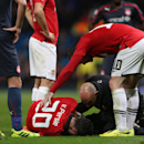 Manchester United's Robin van Persie, bottom, lies injured after colliding with Olympiakos's Kostas Manolas during their Champions League last 16 second leg soccer match at Old Trafford Stadium, Manchester, England, Wednesday, March 19, 2014