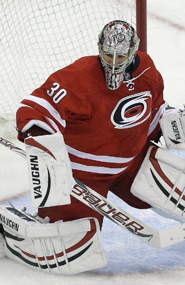 In this photo taken Wednesday, Sept. 18, 2013, Carolina Hurricanes goalie Cam Ward deflects a shot on goal during the third period of a preseason NHL hockey game against the Columbus Blue Jackets in Raleigh, N.C. The NHL's realignment meant the end of the Southeast Division and placed the Hurricanes into the new Metropolitan Division