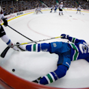 Vancouver Canucks' David Booth, right, falls to the ice after being checked by Colorado Avalanche's Marc-Andre Cliche during first period NHL hockey game in Vancouver, British Columbia on Sunday, Dec. 8, 2013 The Associated Press