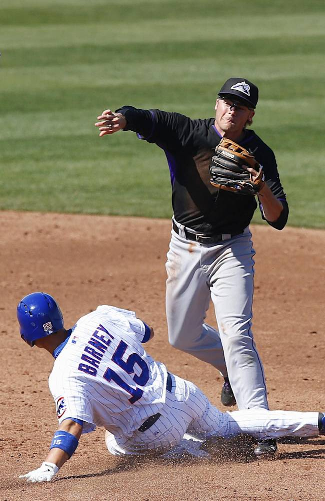 Colorado Rockies' Josh Rutledge, top, throws to first after forcing out Chicago Cubs' Darwin Barney (15) at second base during the third inning of a spring training baseball game Tuesday, March 11, 2014, in Mesa, Ariz. The Rockies defeated the Cubs 13-0