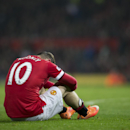 In this Nov. 29, 2014 photo, Manchester United's Wayne Rooney sits on the pitch after being injured during the English Premier League soccer match between Manchester United and Hull City at Old Trafford Stadium, Manchester, England. The Manchester United