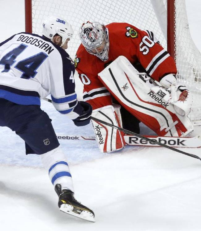 Chicago Blackhawks goalie Corey Crawford (50) makes a save on a shot by Winnipeg Jets defenseman Zach Bogosian (44) during the first period of an NHL hockey game, Sunday, Jan. 26, 2014, in Chicago