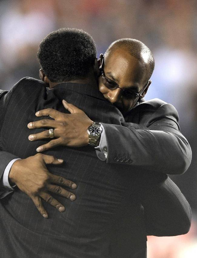 Former Philadelphia Eagles Donovan McNabb, rear, and Brian Dawkins embrace during halftime of an NFL football game between the Eagles and the Kansas City Chiefs, Thursday, Sept. 19, 2013, in Philadelphia. The Eagles retired McNabb's jersey number at halftime